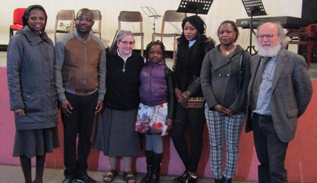"""Suor Alma in posa con una famiglia residente a Olgiate originaria di uno dei paesi africani in cui ha trascorso alcuni anni della sua missione. Primo da destra: Antonello Brivio, direttore della scuola di musica """"Eugenio Nobili""""; prima da sinistra: Suor Evelyn, la consorella di Suor Alma originaria del Ghana."""
